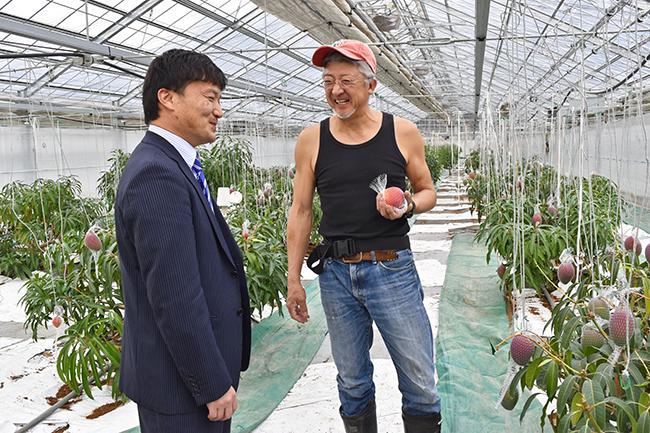 中川代表(右)から収穫状況などを聞く太田智也・同信金地域経済振興部副部長(12月6日、栽培ハウス)