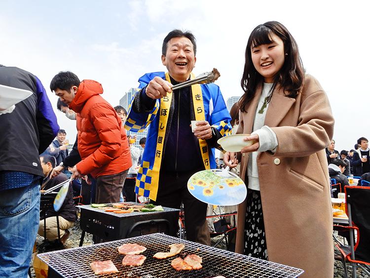 バーベキューで焼いた肉を行員に配る渡邊頭取(3月16日、川崎市多摩川緑地)