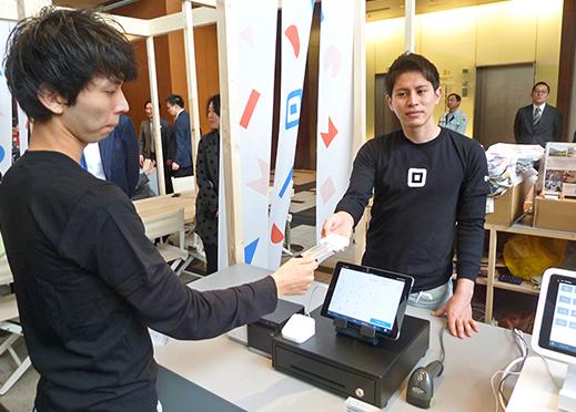 スクエアの決済端末をデモンストレーションでPRする(東京ミッドタウン地下1階イベント会場アトリウム、3月26日)