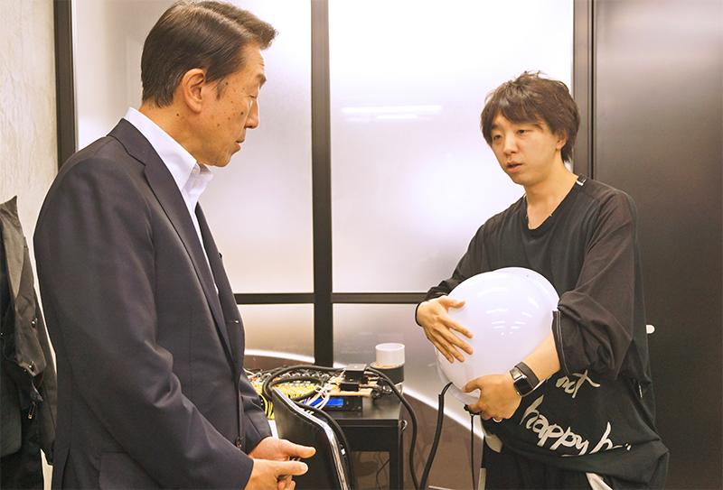聴覚障がい者も波動で音楽を体感できる球体型デバイスの説明を落合氏から聞く関根社長(左、6月4日、東京・神田)