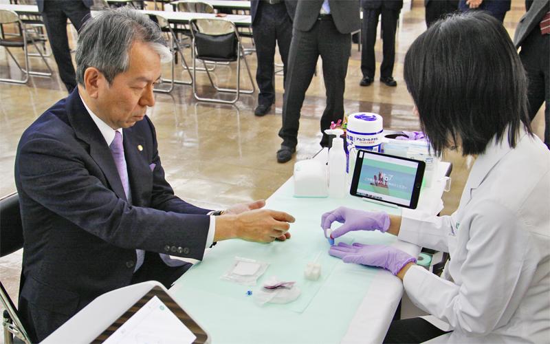 中指からの自己採血に臨む北日本銀行の柴田克洋頭取(左)。左下にあるのが測定機器(11月7日、北日本銀行本店)