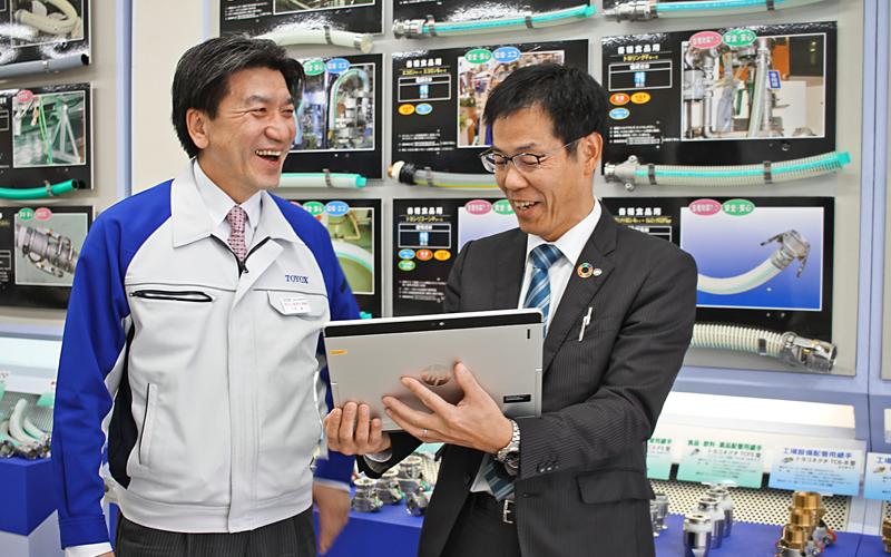 企業型DC導入を支援したトヨックスの中西誠代表取締役(左)と笑顔で商談する松原博史エリア統括(1月16日、トヨックス本社)