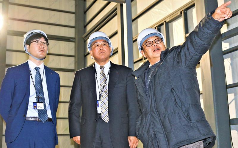 今春、新工場を完成させるSKファームの小舘誠一社長(右)から、施設内を案内される伊藤嘉將支店長(中央)と融資担当の高橋駿太朗さん(1月9日、青森県つがる市)