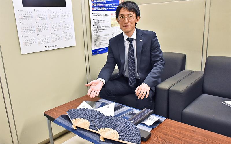 新潟信金は年金顧客の誕生月に地元の伝統織物「亀田縞」を使った製品をプレゼント。第1弾は扇子、今年は風呂敷を贈った(3月11日、新潟信金本部)