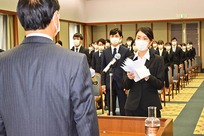 時間を短縮し、全員がマスク着用で開催した宮崎銀行の入行式。平野亘也頭取に決意の言葉を述べる新入行員代表の黒木惇奈さん(4月1日、第一宮銀ビル)