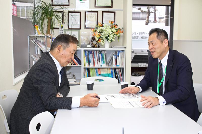 主要取引先の福井住宅流通の間政和社長(左)に提案活動を行う小坂祥久支店長