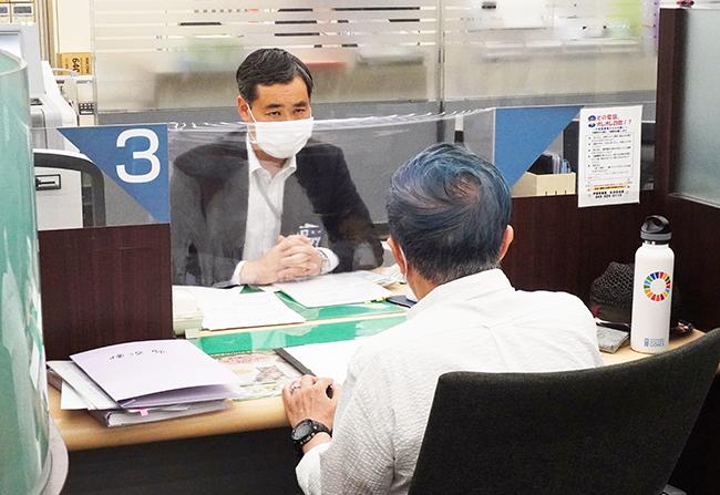 「新型コロナウイルス資金繰り相談窓口」を訪れた融資取引のない事業者の相談に応じる横浜銀行の行員(5月1日、横浜駅前支店)