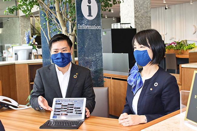 プリーツ型(左)と立体型マスクを着用する行員。鮮やかな藍色で涼しさを演出(6月4日、阿波銀行本店営業部)