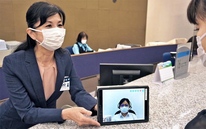 外国人客はタブレット端末の映像通訳を見ながら、行員から手続きやサービスの案内を受ける(5月28日、横浜銀行本店営業部)