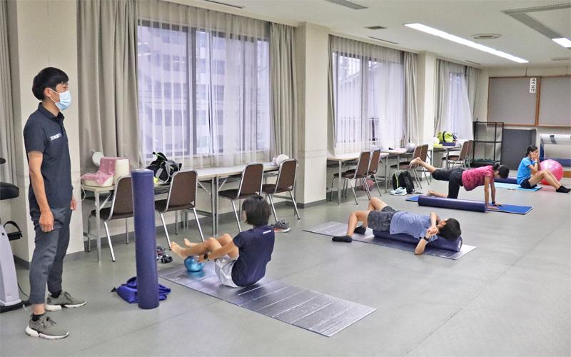 間隔を空けてトレーニングする宮崎銀行女子陸上部の選手。佐伯尚彦監督(左)はマスクを着用(6月12日、宮崎銀行健保会館)
