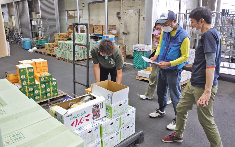 調達する食材を確認する農業法人「春一番」の社員(中央)と「かごしまこども食堂・地域食堂ネットワーク」事務局スタッフ(左、7月9日、中央卸売市場)