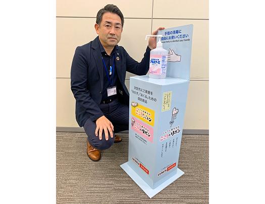 消毒液の台で信託商品を紹介。新たな宣伝ツールとして信金へ提供する(7月29日、高橋次長)