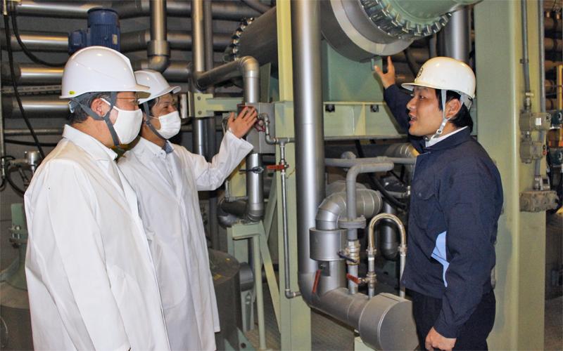 増田政隆代表取締役(右)から設備融資で購入した機械の説明を受ける増田伸宜支店長(左)と担当者(8月4日、増田化学工業)