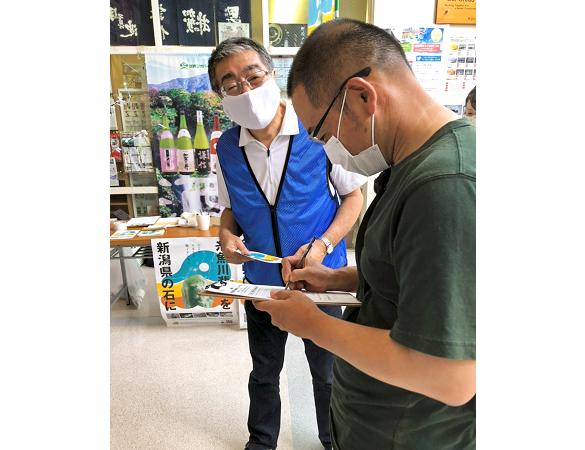 署名を呼び掛ける黒石孝・糸魚川信組理事長(左、9月5日、フォッサマグナミュージアム)