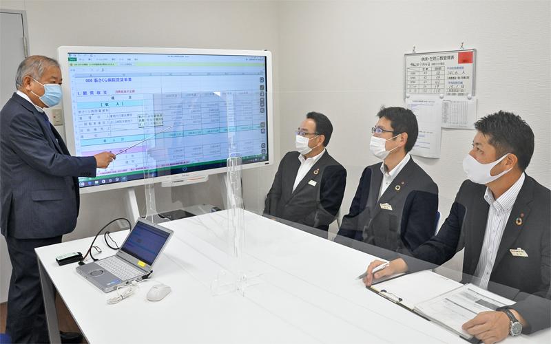 さくら病院の北島秀雄常務理事(左)から決算内容を踏まえた経営状況についてレクチャーを受けた白浜和也支店長(左から2人目)と担当者(9月14日、さくら病院)