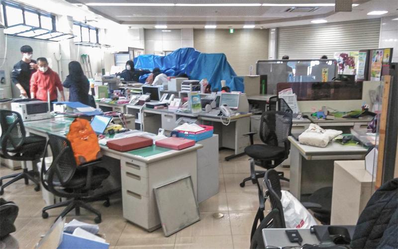 空調設備から漏れ出した冷却用の水を処理する福島信金の職員(2月14日、福島信金梁川支店)