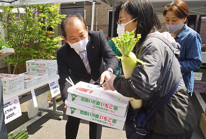 即売会では鹿沼相互信用金庫の協力で栃木県鹿沼市産イチゴ「とちあいか」も出品・完売。買い物客を手伝う土屋理事長(4月15日)