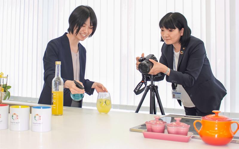 出店者の商品を紹介する写真を撮影する阿波銀行コネクト社員(6月17日、徳島市)