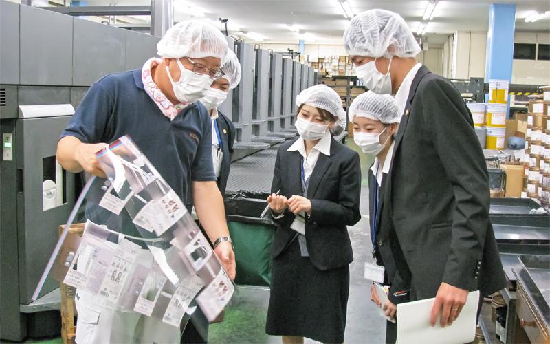 工場現場で実際の作業を見学、「書類だけではわからないことを知ることができた」とエール印刷の榊原啓太代表取締役(左)の説明を聞く吉田支店の職員(6月24日、エール印刷本社)