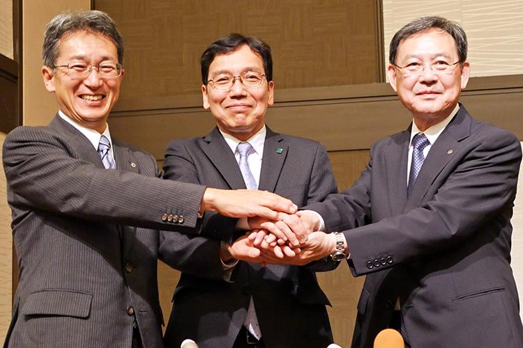 統合会見で握手する(左から)伊藤新・北都銀行頭取、田尾祐一・フィデアHD社長、村上・東北銀行頭取(7月2日、仙台市内)
