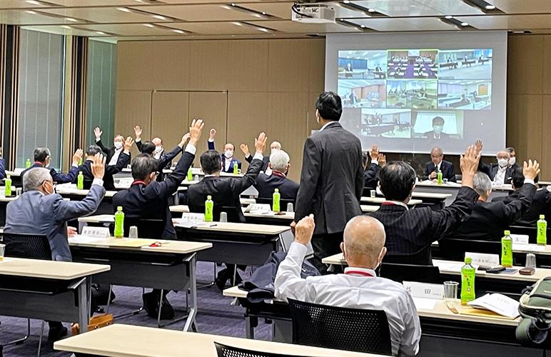 ウェブ会議システムでつないだ地区会場ごとに議案の賛否を挙手で確認した(6月29日、全国信用組合会館)