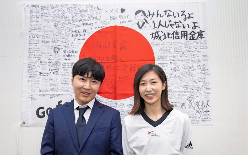 役職員の寄せ書きを添えた日本国旗の前に立つ城北信金の大前理事長(左)と山田選手(7月7日、本部)
