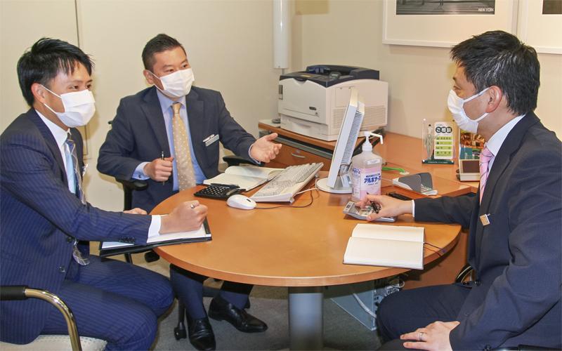 渉外担当者のチームリーダーと富裕層への推進手法を確認する中田哲也支店長(中央、7月2日