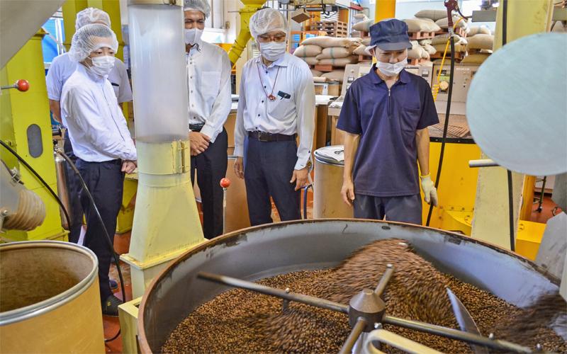ダートコーヒーの中西泰仁業務部長(右から2人目)からコーヒー豆の焙煎工程などのレクチャーを受ける北川昌志支店長(同3人目)と小林義和支店長代理(左、7月16日、ダートコーヒー白山工場)