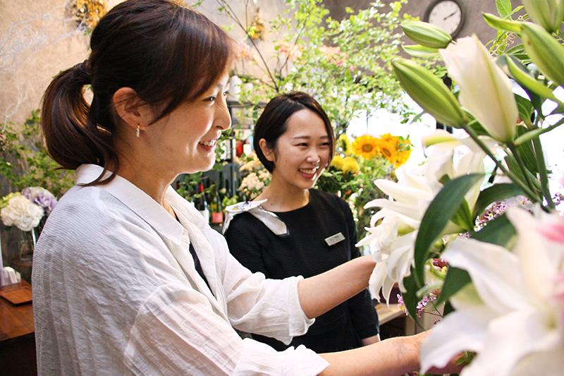 巣鴨信金の谷口さん(右)に季節の花を説明する堀野さん。産地や品種にこだわる(7月16日、ジフィー)