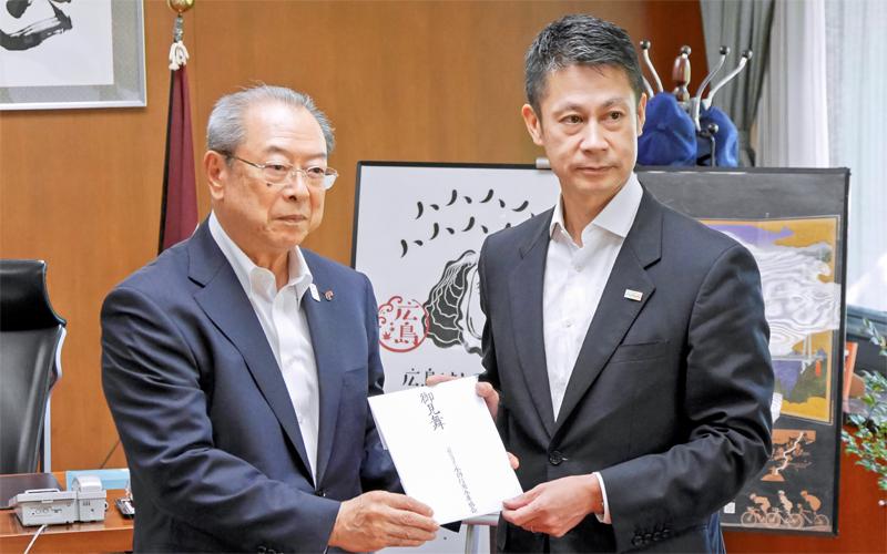 全国の信金役職員などから募った西日本豪雨被害の見舞金を手渡した佐藤浩二・前全信協会長(左、2018年9月28日、広島県庁)